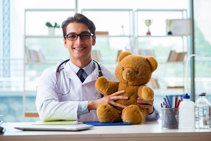 Pediatra z zabawkarskim obsiadaniem w biurze obrazy stock