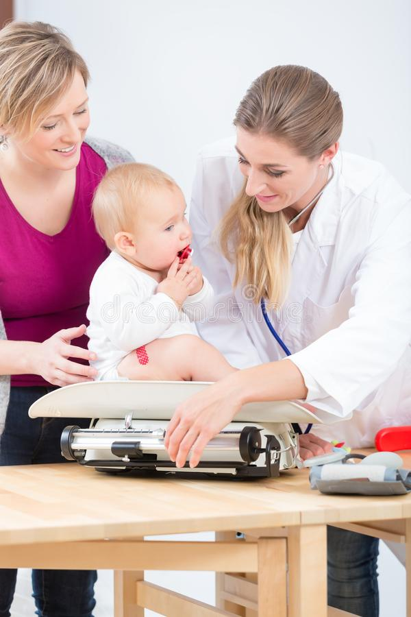 Pediatric care specialist smiling while measuring the weight of a baby girl stock photo