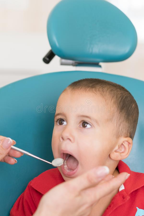 Pediatric dentist examining a little boys teeth in the dentists chair at the dental clinic. Dentist examining little boy& x27;s. Teeth in clinic. vertical photo stock photography