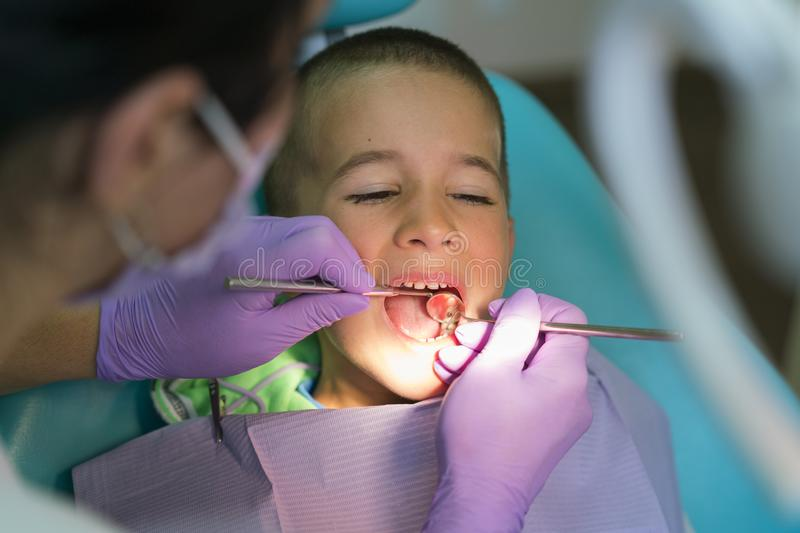 Pediatric dentist examining a little boys teeth in the dentists chair at the dental clinic. A child with a dentist in a royalty free stock photo
