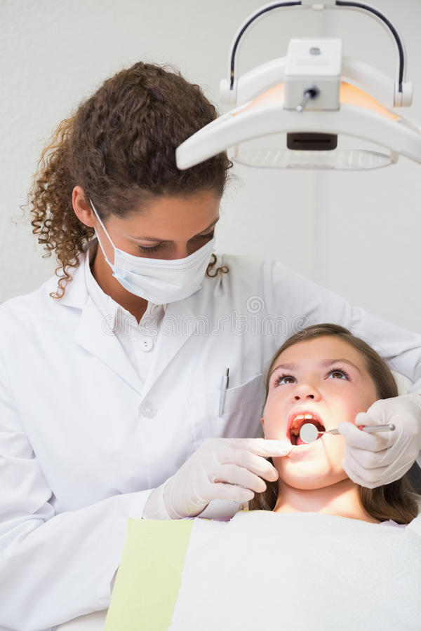 Pediatric dentist examining a little girls teeth in the dentists chair royalty free stock images