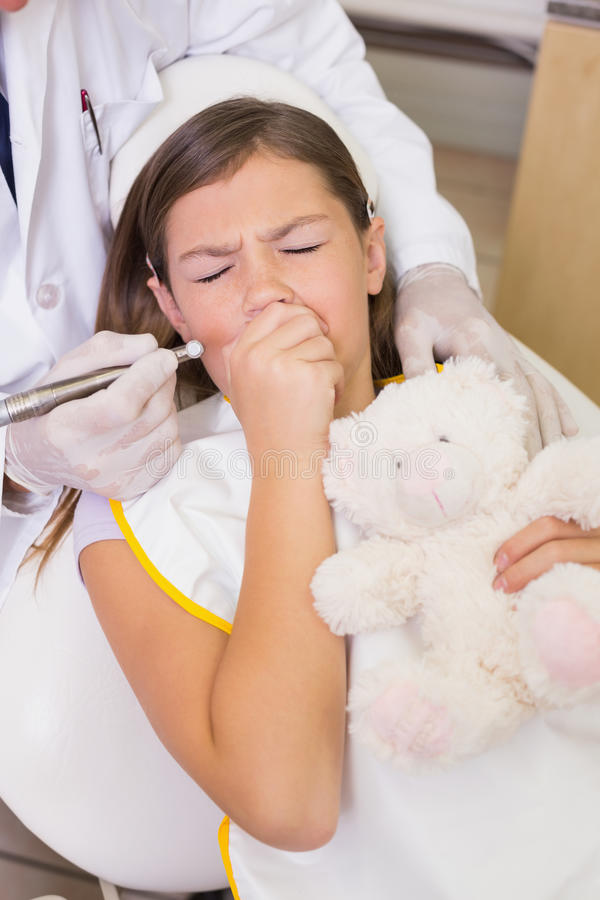 Pediatric dentist trying to see coughing patients teeth. At the dental clinic royalty free stock photo