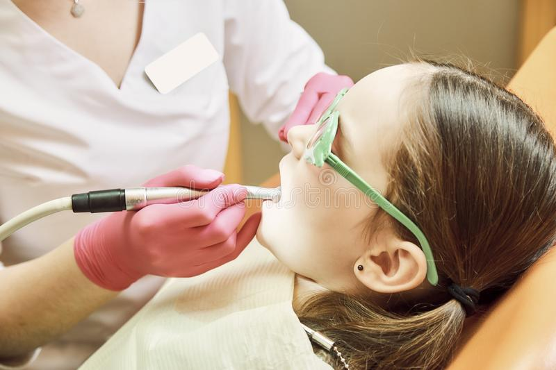 Pediatric dentistry. Dentist treats teeth of little girl royalty free stock photography