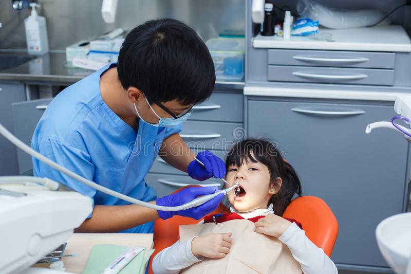 Pediatric dentistry, prevention dentistry concept. Dentist clean. Ing little Asian girl`s teeth. Oral hygiene stock photos