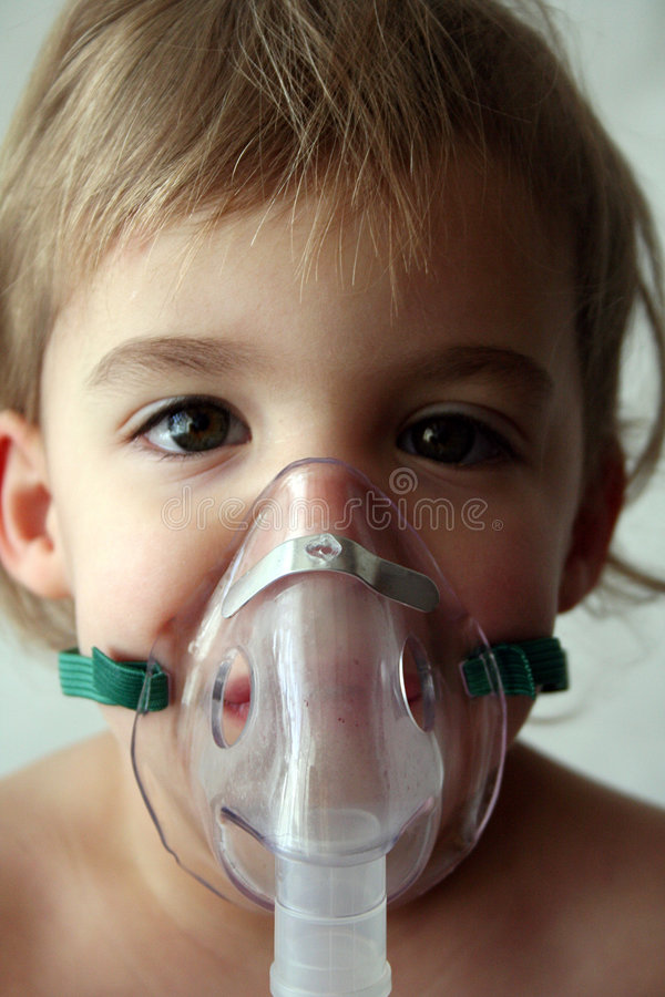 Pediatric Nebulizer Treatment. A little girl looks at the camera while taking her nebulizer breathing treatment stock photos