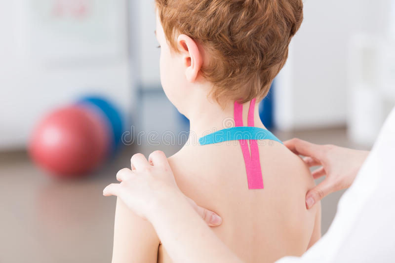 Pediatric physiotherapy and kinesiotaping. Little crooked boy with spine problems having kinesiotaping on his cervical spine. Physiotherapist exercising with stock photography