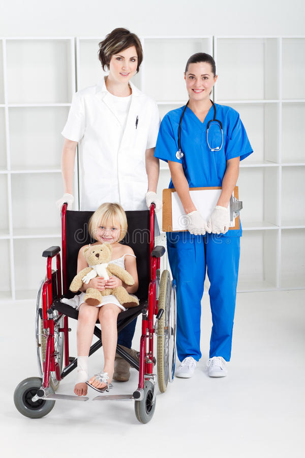 Pediatric ward. A caring medical team with a young girl with broken foot in wheelchair in pediatric ward royalty free stock image