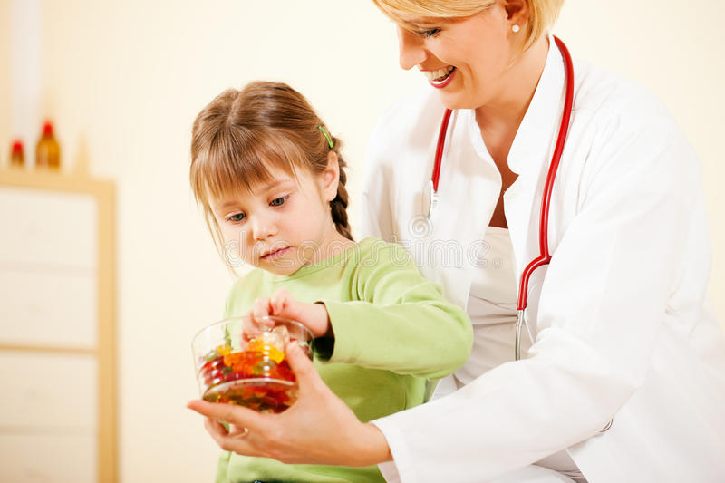 Pediatrician Doctor Giving Candy To Little Patient Editorial Image