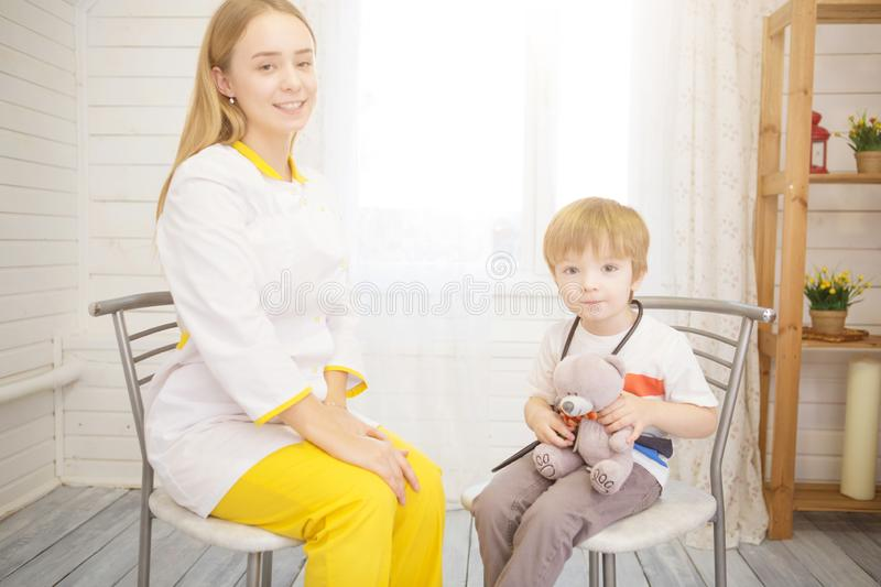 Doctor using stethoscope to listen to kid and checking heart beat stock photography