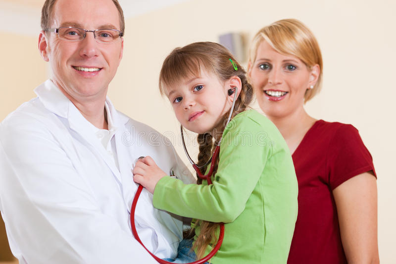 Pediatrician With Family In His Surgery Royalty Free Stock Photos