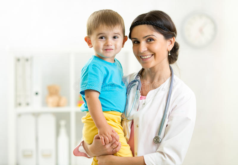 Pediatrician female doctor holding in her hands kid royalty free stock photos