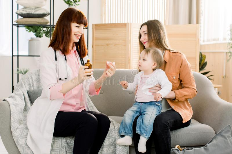 Pediatrician giving spoon dose of medicine liquid drinking syrup to baby patient stock image