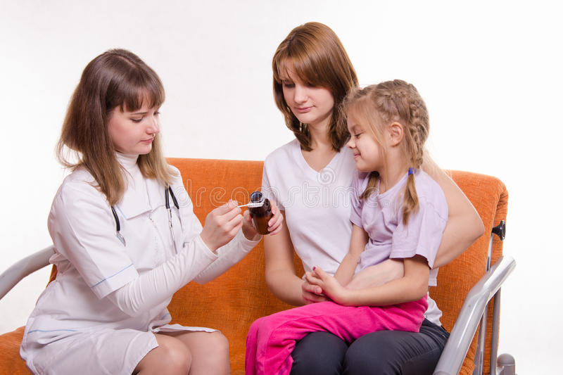 Pediatrician is going to give a sick child sitting on hands at mother medicine from spoon stock photo