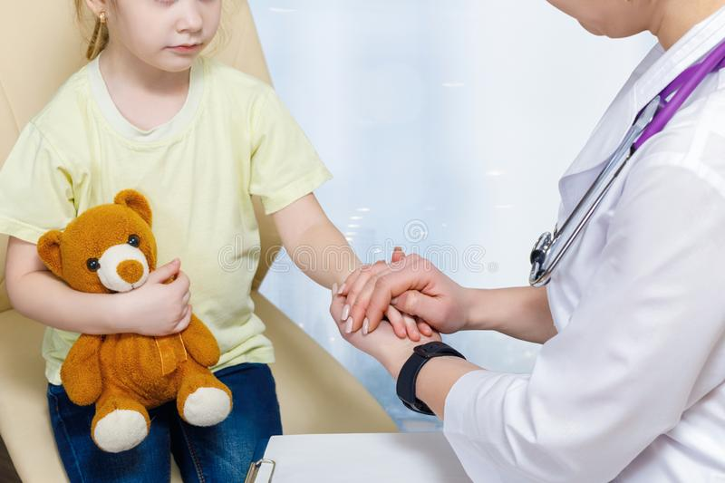 Pediatrician is holding a hand of a small child in protective gesture royalty free stock image