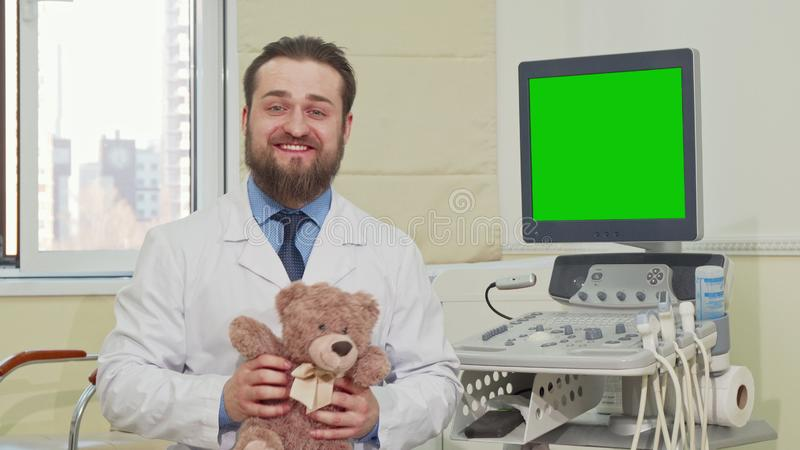Pediatrician holding teddy bear, ultrasound scanner with green screen on the back. Pediatrician holding teddy bear, ultrasound scanner with green chroma key stock images