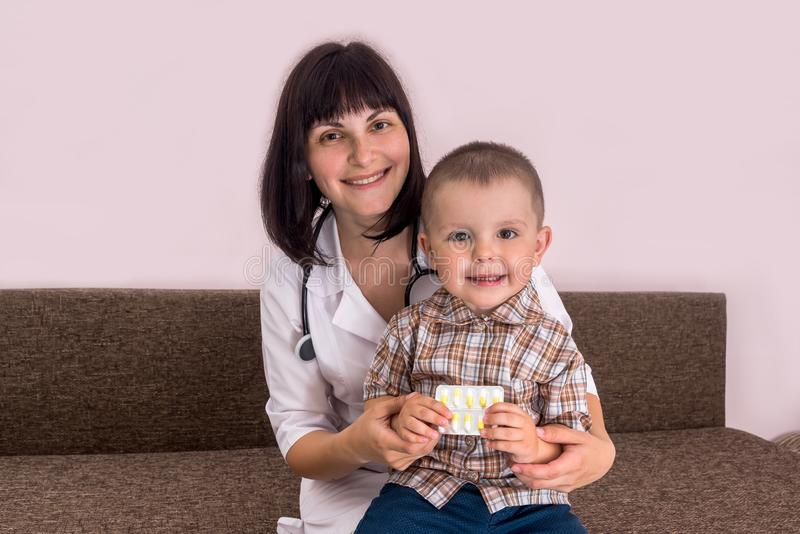 Pediatrician with little boy sitting on knees holding pills stock photos