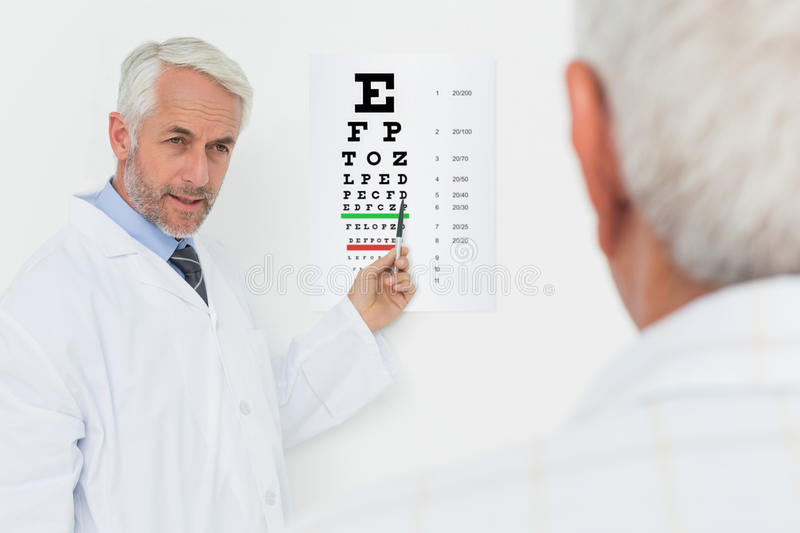 Pediatrician ophthalmologist with senior patient pointing at eye chart. Male pediatrician ophthalmologist with senior patient pointing at eye chart in medical stock photography