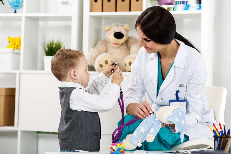 Pediatrician with patient. Family doctor examination. Little child visiting pediatrician playing with stethoscope. Beautiful female medical freckled doctor stock photography