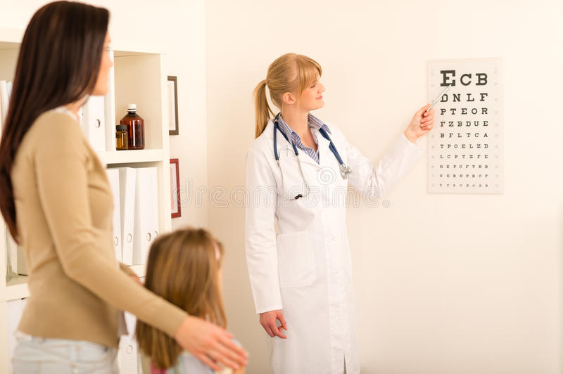 Pediatrician pointing eye-chart at medical office royalty free stock images
