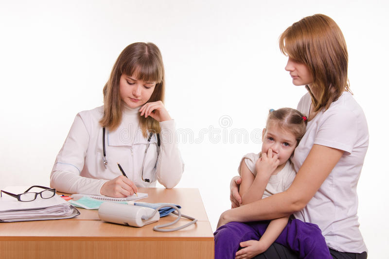 Pediatrician writes appointment for treatment sick child stock photos