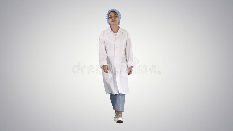 Pediatricion de sorriso que guarda as mãos em uns bolsos do uniforme e que anda no fundo do inclinação fotos de stock