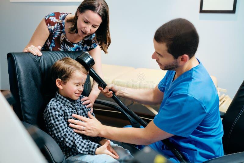 Pediatrikerdoktor Doing Brain Treatment To Autistic Child i klinik royaltyfri bild