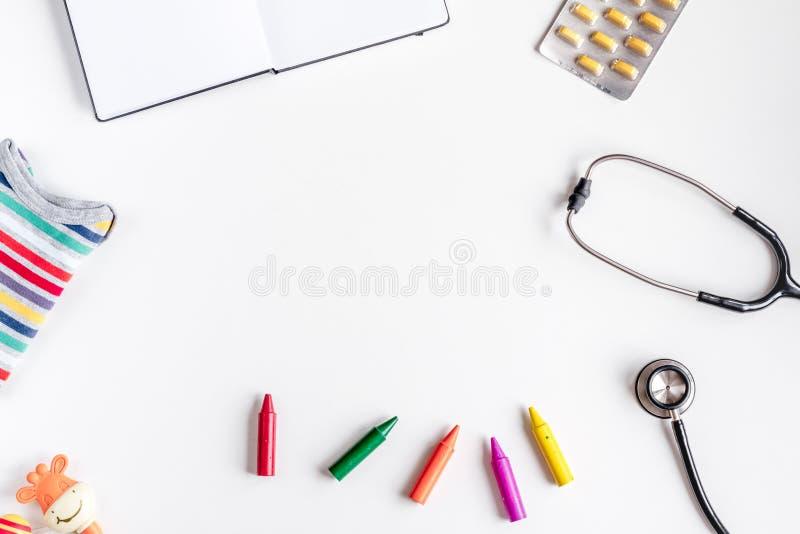 Pediatrikutrustning med färgpennor, utrymme för bästa sikt för bakgrund för stetoskop vitt för text arkivfoton