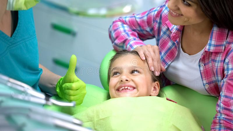 Pediatrische tandarts die duim-omhoog aan weinig patiënt na regelmatige controle tonen stock afbeeldingen