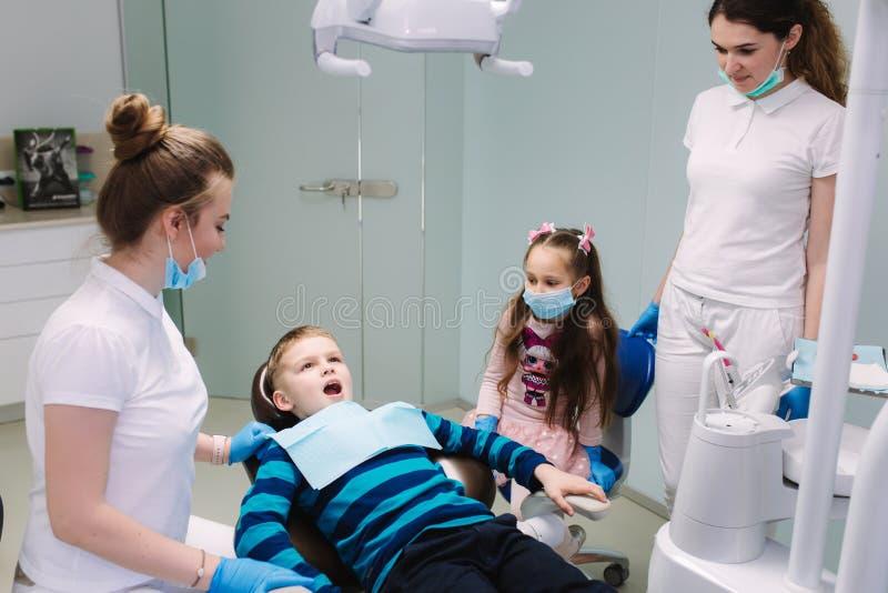 Pediatrische tandarts met medewerker met weinig jongen en meisje stock foto's