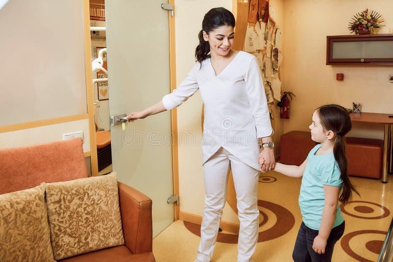 Pediatrische Tandheelkunde De tandarts nodigt het meisje aan het bureau uit royalty-vrije stock afbeeldingen