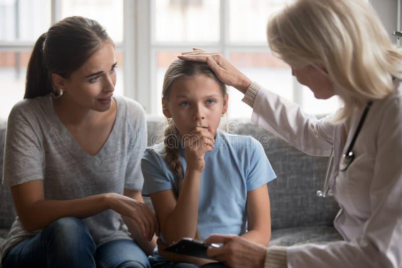 Pediatrisk doktor som slår huvudet av den lilla sjuka flickan under besök fotografering för bildbyråer