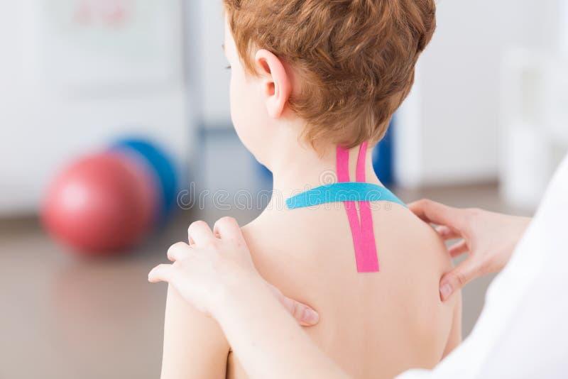 Pediatrisk sjukgymnastik och kinesiotaping arkivbild