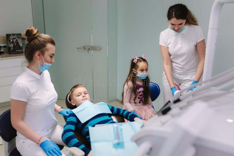 Pediatrisk tandläkare med assistenten med pysen och flickan arkivbilder