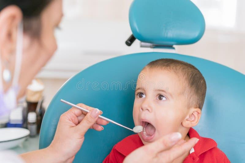 Pediatrisk tandläkare som lite undersöker pojketänder i tandläkarestolen på den tand- kliniken Tandläkare som undersöker liten bo arkivbilder