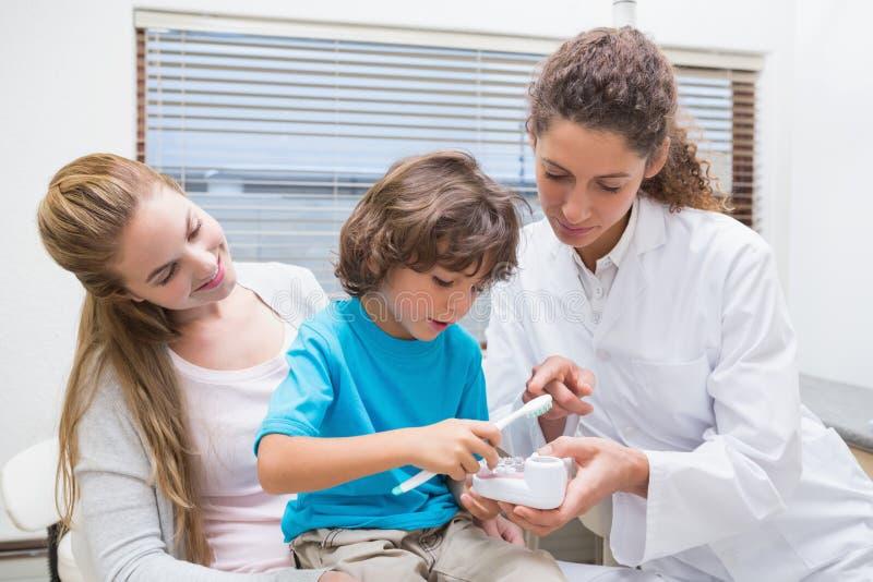 Pediatrisk tandläkarevisningpys hur man borstar tänder med hans moder arkivbild