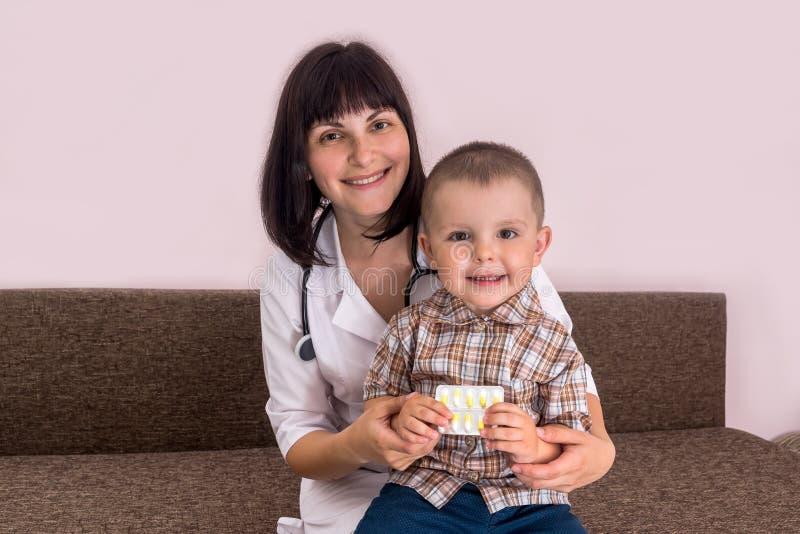 Pediatriskt med pysen som sitter på knä som rymmer piller arkivfoton