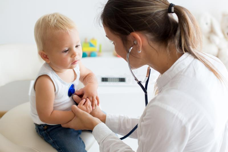 Pediatriskt undersöka behandla som ett barn pojken Doktor som använder stetoskopet till lis royaltyfri fotografi