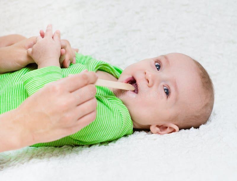 Pediatriskt undersöker ett nyfött behandla som ett barn med en spatel royaltyfri foto
