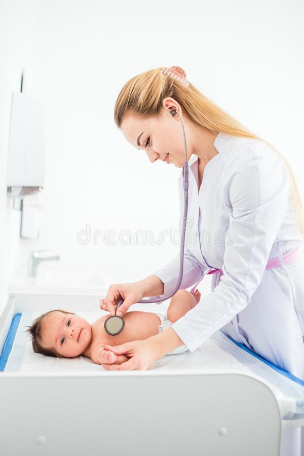 Pediatriskt undersöker två månad behandla som ett barn flickan Manipulera genom att använda en stetoskop för att lyssna till baby arkivbilder
