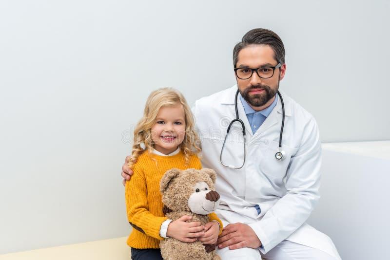 pediatrist con la niña y su oso de peluche que se sienta en el sofá foto de archivo libre de regalías