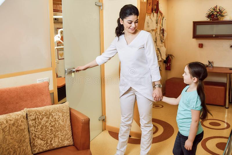 Pediatryczna dentystyka Dentysta zaprasza dziewczyny biuro obrazy royalty free