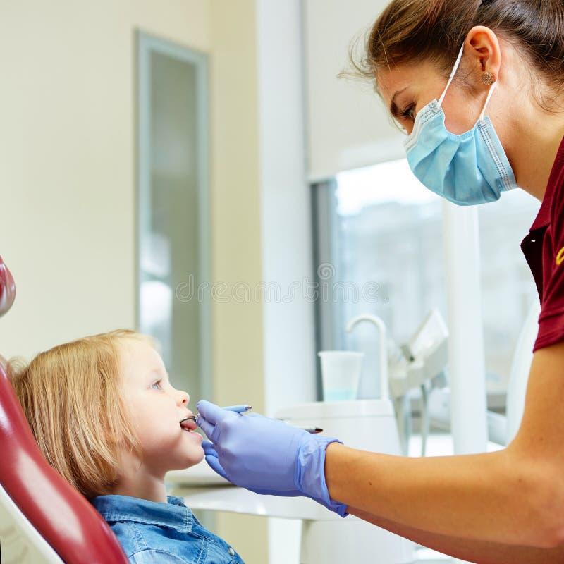 Pediatryczny dentysta egzamininuje mała dziewczynka zęby wewnątrz zdjęcia stock