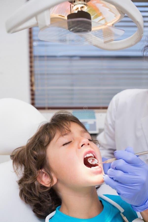 Pediatryczny dentysta egzamininuje troszkę chłopiec zęby w dentysty krześle obrazy royalty free