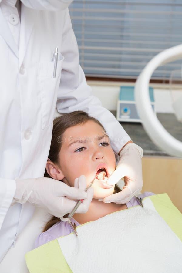 Pediatryczny dentysta egzamininuje troszkę dziewczyna zęby w dentysty krześle obrazy stock