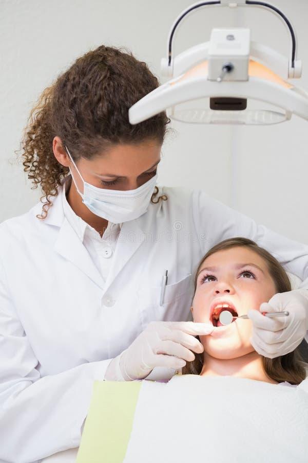 Pediatryczny dentysta egzamininuje troszkę dziewczyna zęby w dentysty krześle obrazy royalty free