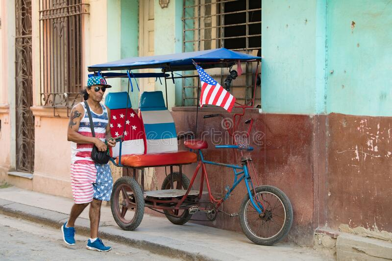 Pedicab, bikecab, velotaxi, cycle with flag of USA and seats , drivers shirt, cap, shorts with stars and stripes, Havana, Cuba.. stock photo