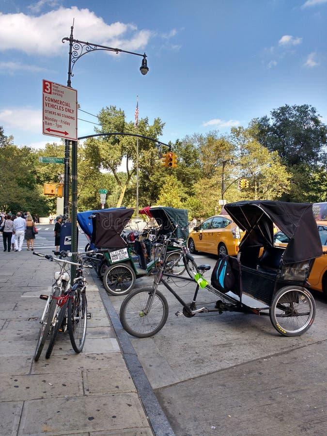 Pedicabs estacionou na 6a avenida perto do Central Park, New York City, NYC, NY, EUA fotografia de stock royalty free