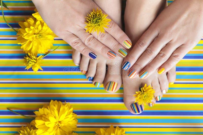 Pedicuras y manicuras rayadas coloridas del verano de la moda fotos de archivo