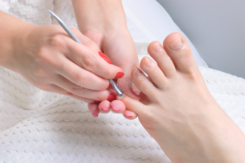 Pedicure applying stock images
