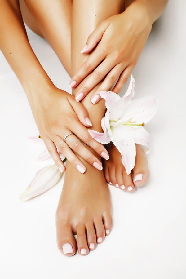 Pedicure del manicure con la fine del giglio del fiore su isolata su pe bianco immagine stock libera da diritti